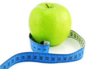 Bright green apple and measuring tape