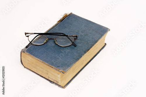 Very old book with reading glasses resting on white