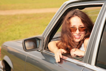 Woman smiles having turned back in a car window