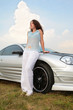 Woman stands having leant on a sport car