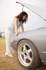 Woman looks under a car cowl