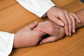 Hand einer Pflegerin und einer alten Seniorin