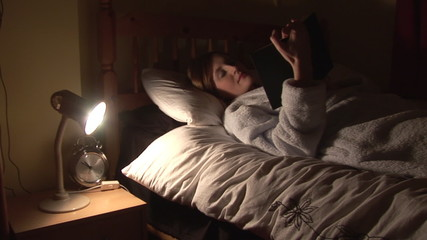 Footage of beautiful woman reading in bed at night