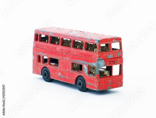 Old red paint peeling toy double decker bus. - 12033847
