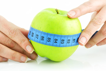 Woman's hands holding bright green apple and measuring tape isol