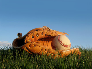 Baseball glove with ball resting in a grass field