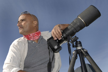 Handsome photographer posing with is big camera outdoors