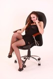 Girl in stockings on armchair with mobile phone