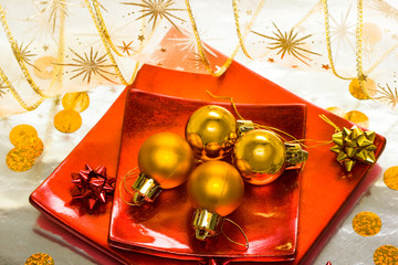 golden Christmas balls on red plate