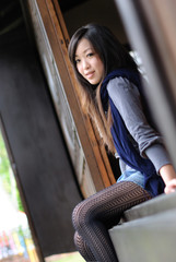 Beautiful young lady setting on the japanese wooden door
