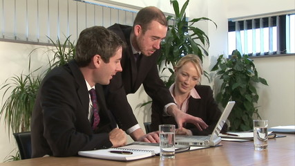 A businessman discusses a project with two other business people