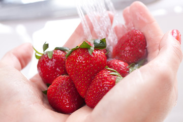 Hands Rinsing Strawberries