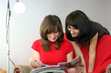 young two women in reading magazine