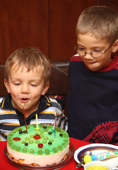 Two boys is blowing candles