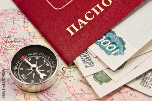 Passport with the money and compass on a map Russia