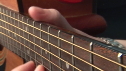 Fingers playing the strings of a guitar
