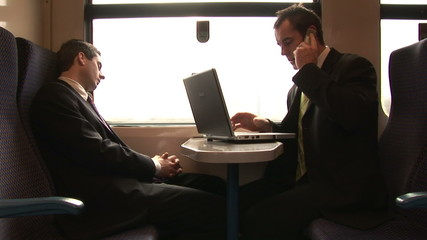 Businessman working in a train while his colleague is sleeping