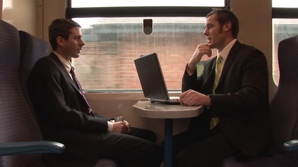 Two businesmen having a conversation in a train