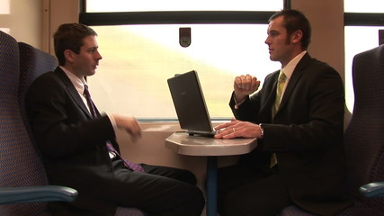 Businessmen working in a train with a laptop