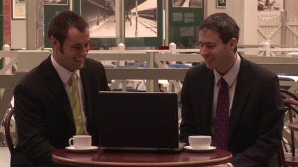 Businessmen talking in a bar and using a laptop