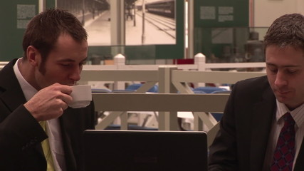 Businessmen having coffee and using a laptop footage