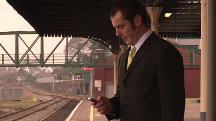 Footage of a businessman sending a text in a train station