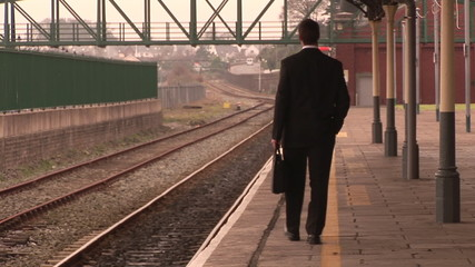 Businessman on phone walking in a train station
