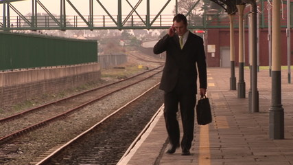 Businessman walking and speaking on a mobile in a station