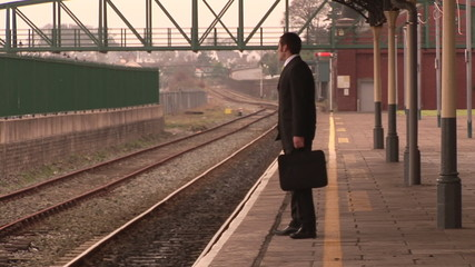 Footage of a businessman waiting for a train in a station