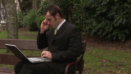 Busy businessman on phone and working with laptop outdoors