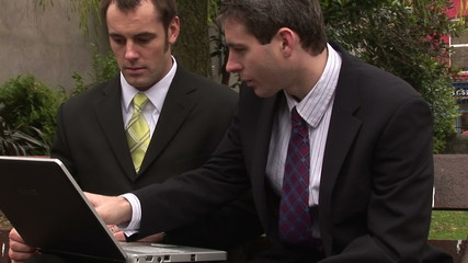 Two businessmen working with a laptop in a park