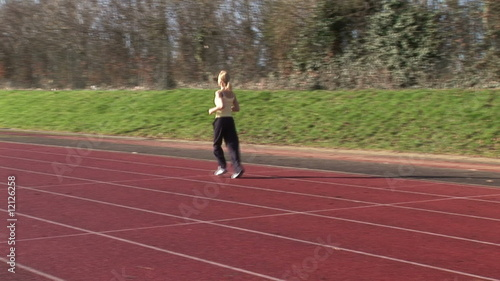 Beautiful blonde running on a racetrack