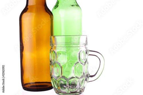 Tankard and bottles of beer on white background