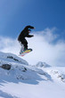 Male snowboarder jumping of a hill