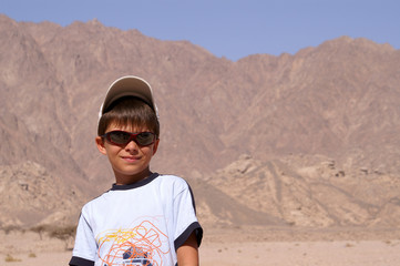 Young boy standing on mountains with blue sky in background