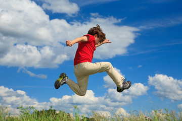Kid running, jumping on green meadow against blue sky