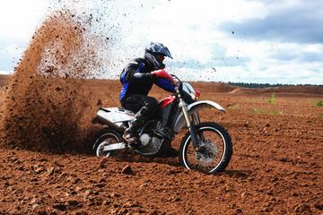 Off-road motorbike driving in dirt.