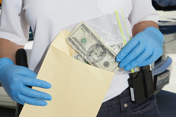 Police Officer Putting Money in Evidence Envelope