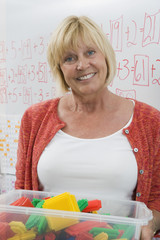 Teacher Holding a Box Full of Plastic Puzzle Pieces