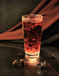 Glass with hot red tea on a background of a drapery.