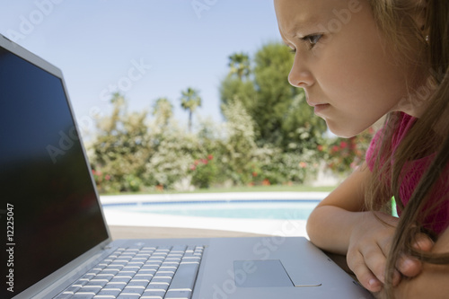 Serious Little Girl Using a Laptop