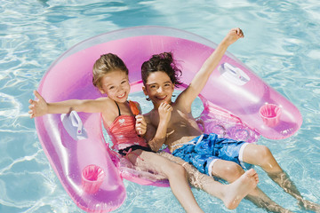 Children Playing on Inflatable Toy in Swimming Pool