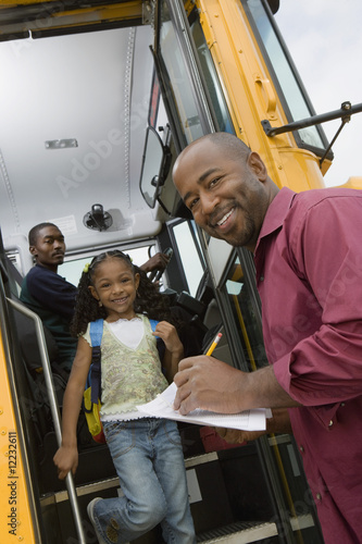 Teacher Unloading Elementary Students from School Bus