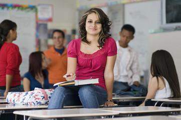 High School Student Sitting on a Desk