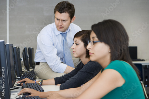 Teacher Helping Computer Students