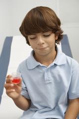 Boy holding liquid medicine