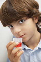 Boy holding medicine in liquid measure,portrait
