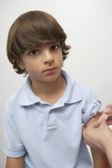 Nurse placing bandage on boy's arm