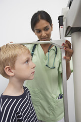 Young female doctor measuring boy's height