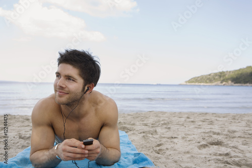 ibiza, young man listening to mp3 player on beach